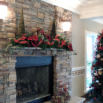 Beautiful brick fireplace in the Jaxson Banquet Hall decorated for Christmas with a festive green garland with red sparkly bows