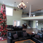 Spaciaous lodge with comfy blak leather couches, second story balcony overlooking the living area and a giant Christmas tree in the left hand side decorated in sparkling white lights, red bows, and colorful streamers and ornaments