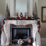 Beautiful brick fireplace decorated with festive red and green christmas decoration and white Christmas trees in the Naimoli Estate mansion